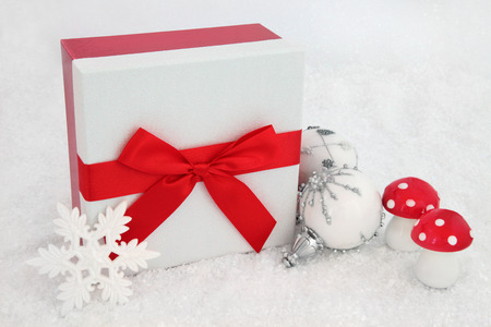 white fly: Christmas glitter gift box with red bow, white snowflake baubles and fly agaric decorations on snow background.