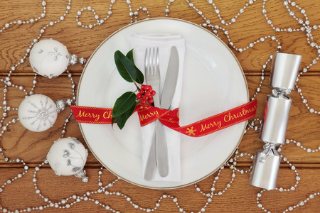 serviette: Christmas table setting with white porcelain plate, knife and fork, linen serviette, merry christmas red ribbon, silver bauble decorations and cracker over oak background. Stock Photo