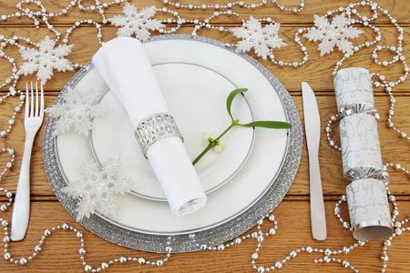 servilleta de papel: ajuste de la tabla de la cena de Navidad espumoso blanco con placas de porcelana, cubiertos, servilleta y anillo, mu�rdago, copo de nieve chucher�a plata y adornos de perlas con la galleta m�s de fondo de roble. Foto de archivo