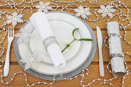 serviette: Sparkling christmas dinner table setting with white porcelain plates, cutlery, serviette and ring, mistletoe, silver bauble snowflake and bead decorations with cracker over oak background.