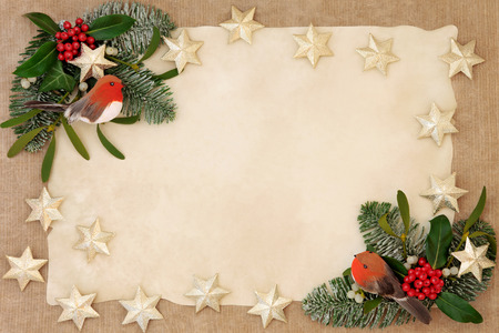 christmas robin: Christmas decorative background border with gold star and robin decorations, holly, ivy, mistletoe, snow covered  fir over old parchment and hemp paper. Stock Photo