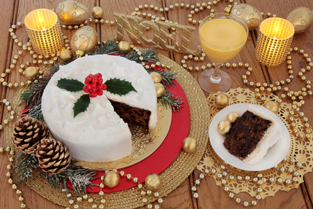 egg nog: Christmas cake and slice, with egg nog, holly berries, candles, noel glitter sign, gold bauble decorations and foil wrapped chocolates with bead strands over oak table background. Stock Photo