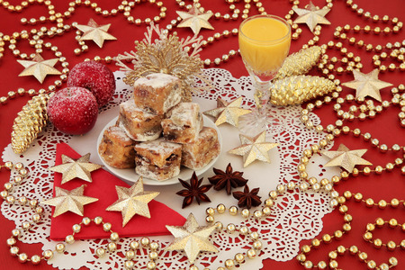 gold christmas decorations: Christmas stollen cake bites, advocaat egg nog and gold bauble  decorations on a red background.
