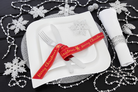 napkin ring: Modern christmas table setting with square porcelain plates, red ribbon, cutlery, napkin and ring with silver snowflake and bead chain decorations over dark wood background. Stock Photo