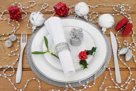 servilleta de papel: Christmas dinner place setting with white porcelain plates, knife and fork, linen serviette with silver ring, bauble decorations, holly and mistletoe over oak background. Foto de archivo