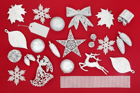 Christmas symbols in silver of tree decorations and baubles over red background.