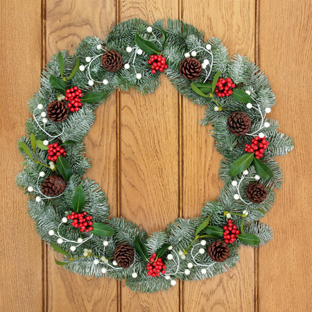 christmastide: Christmas wreath with holly, mistletoe, pine cones and snow covered blue spruce fir over oak wood front door background.