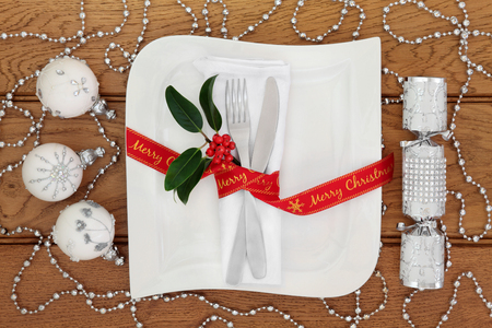 serviette: Christmas dinner table setting with white porcelain square plate, knife and fork, linen serviette, red merry christmas  ribbon, silver bauble decorations and cracker over oak background.