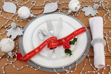 servilleta de papel: Christmas dinner table setting with porcelain plates, red ribbon, knife and fork, linen serviette,  holly, with silver and white bauble decorations over oak background.