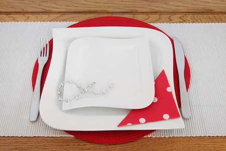 serviette: Elegant table setting with white porcelain plates, cutlery, decorative bead chain, polka dot serviette on red placemat and silver runner on oak background. Stock Photo