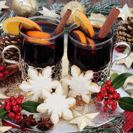 gold christmas decorations: Christmas party food and drink with mulled wine, gingerbread biscuits, with gold bauble decorations, spices, fruit, holly and snow covered fir. Stock Photo
