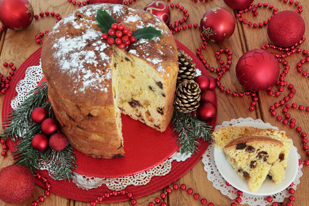 Traditional Italian panettone christmas cake and slice with holly berries, pine cones, red bauble decorations and bead strands over oak table background.