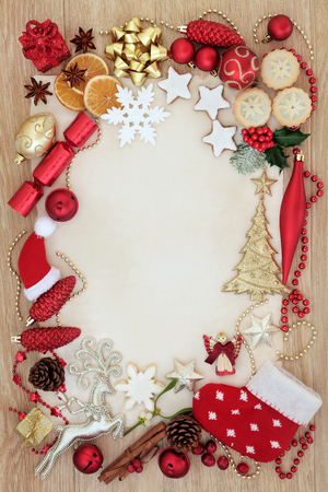 Christmas abstract background border with tree decorations and baubles, gingerbread biscuits, mince pies, orange and cranberry fruit on parchment paper over oak wood.