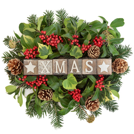 Christmas decoration with xmas sign in old wooden blocks, holly, ivy, gold pine cones and fir leaf sprigs over white background. Stock Photo