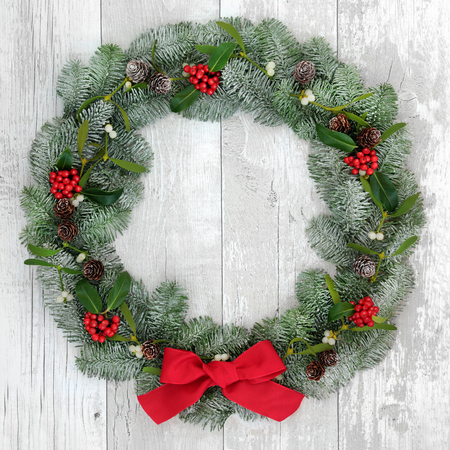 distressed background: Traditional christmas wreath decoration with holly, fir and mistletoe over distressed white wood front door background. Stock Photo