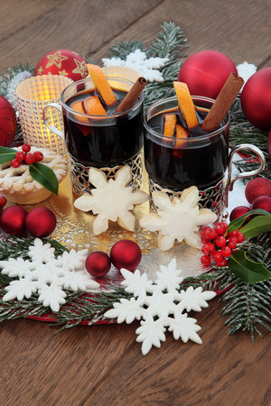 candlelit: Christmas mulled wine, gingerbread biscuits, snowflake and red bauble decorations, candles, holly and snow covered fir over oak background.