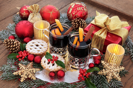 candlelit: Christmas still life with food and drink of mulled wine, mince pies, gold snowflake and red bauble decorations, gift box, candles, holly and snow covered fir on oak background.