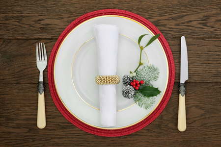 napkin ring: Christmas dinner table setting with gold rimmed white porcelain plate, antique cutlery, napkin and ring, holly, mistletoe, fir and pine cones on red mat over oak background.
