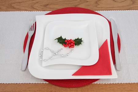 Modern christmas table setting with square wave porcelain plates, stainless steel cutlery, red napkin and silver bead chain on place mats over oak background.