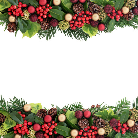 Christmas background border with red and gold bauble decorations, holly, ivy, pine cones, cedar cypress and fir leaf sprigs over white with copy space.
