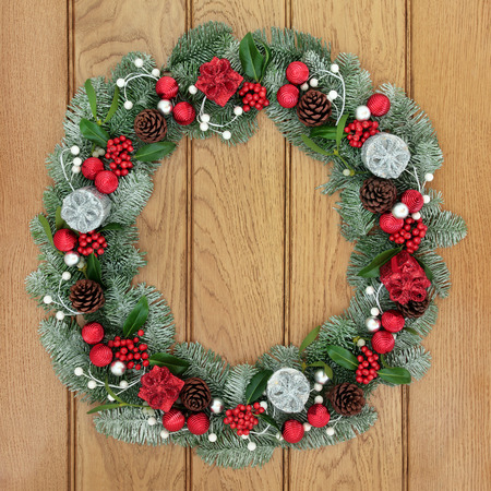 christmastide: Christmas and advent wreath decoration with red and silver bauble and gift box decorations, holly, mistletoe, pine cones and snow covered evergreen blue spruce fir on oak wood front door background. Stock Photo