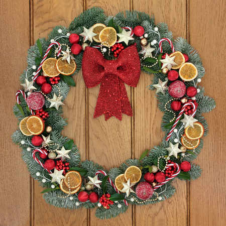 fruit candy: Christmas wreath decoration with gold star and red bow bauble decorations, candy canes, dried fruit, holly, snow covered blue spruce fir and mistletoe over oak wood front door background. Stock Photo