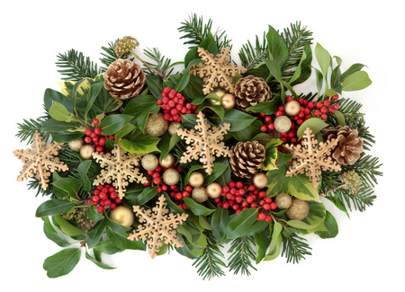 Christmas decoration with gold snowflake and round bauble decorations, holly and red berries, ivy, gold pine cones and fir leaf sprigs over white background. Stock Photo
