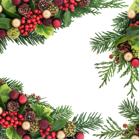 Centrepiece: Decorative christmas border with red and gold bauble decorations, holly and berries, ivy, pine cones, cedar cypress  and fir leaf sprigs over white background with copy space.