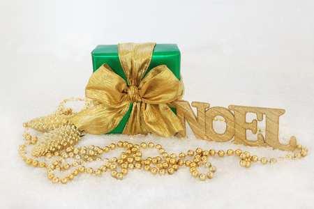 gold christmas decorations: Christmas gift box with gold bow, glitter noel sign, pine cone baubles and bead decorations on snow background.