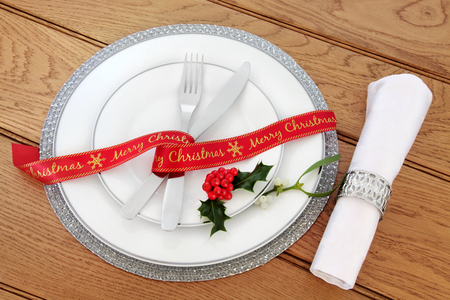 serviette: Simple christmas dinner table setting with white porcelain plates, red ribbon, knife and fork, linen serviette and silver ring and holly over oak background.