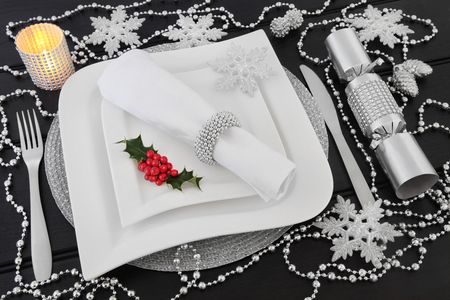 diamond candle: Christmas dinner table setting with white porcelain plates, holly, silver bead decorations, candle, cutlery, linen napkin with ring and cracker over dark wood background.