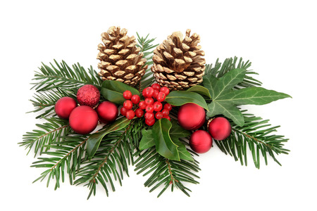 arrangements: Christmas decoration with red baubles, holly, ivy, gold pine cones and winter greenery over white background. Stock Photo