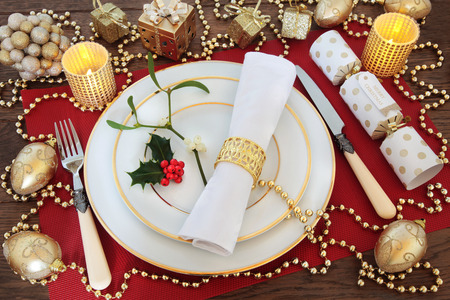 serviette: Christmas dinner table setting with white plates, antique knife and fork, linen serviette, holly, mistletoe, gold bauble decorations, candles, and cracker on red place mat over oak background. Stock Photo