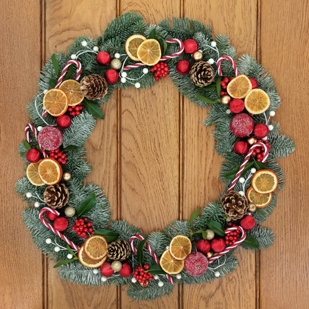 pine  fruit: Christmas snow covered fir wreath decoration with dried orange fruit, candy canes, red and gold baubles, holly, mistletoe and pine cones on oak front door background. Stock Photo