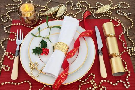 servilleta de papel: Lujo mesa de la cena de Navidad en blanco con placas, cubiertos, servilleta de lino antiguo, acebo, muérdago, Decoraciones de la chuchería de oro, velas, cintas y cracker en la estera de lugar roja sobre el fondo de roble. Foto de archivo