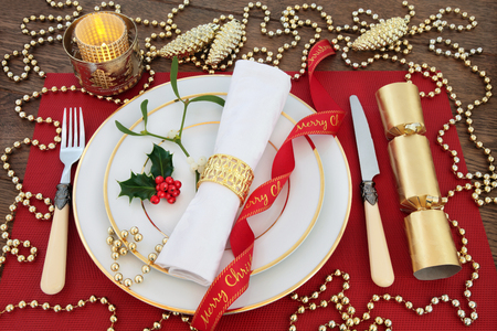serviette: Luxury christmas dinner table setting with white plates, antique cutlery, linen serviette, holly, mistletoe, gold bauble decorations, candle, ribbon and cracker on red place mat over oak background.