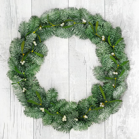 distressed background: Christmas spruce fir and mistletoe wreath decoration over distressed white wood front door background.
