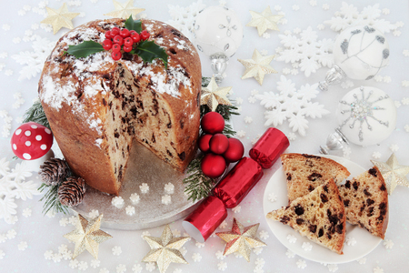 white fly: Chocolate panettone christmas cake and slice with holly berries, cracker, red, silver, gold and white snowflake, round and star shaped bauble decorations and fly agaric mushroom ornament.