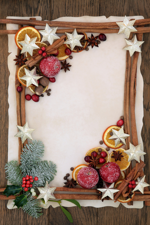 cranberry fruit: Christmas abstract background border with gold star decorations, cinnamon sticks, spices, dried orange, apple and cranberry fruit with holly, fir and mistletoe on parchment paper over oak wood.