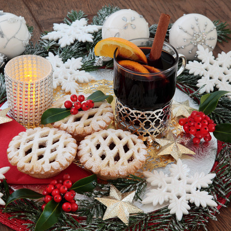 gold christmas decorations: Christmas mulled win and mince pies, with white glitter snowflake and gold star bauble decorations, fruit, holly and snow covered fir over oak background.