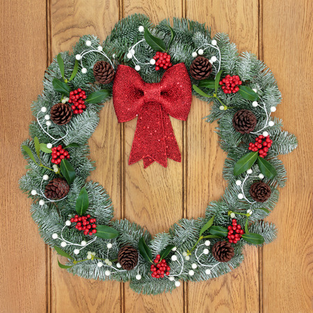 christmastide: Christmas wreath with red bow decoration, holly, mistletoe, pine cones and snow covered blue spruce fir over oak wood front door background.