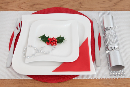 serviette: Christmas dinner table setting with white porcelain plates, holly, cutlery, serviette, silver bead strand and cracker with diamond decoration over oak background.