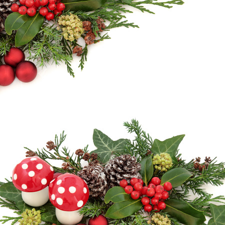 Fantasy christmas background border with fly agaric mushroom decorations, red baubles, holly, ivy, snow covered pine cones and winter greenery over white. Stock Photo