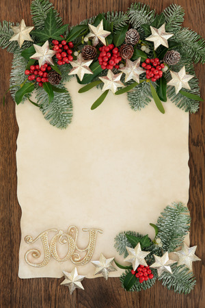 christmas star: Christmas abstract background border with gold glitter joy sign and star decorations,  holly, ivy, mistletoe and snow covered fir on parchment paper over oak.