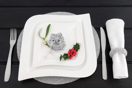 servilleta de papel: Christmas dinner table setting with white china plates, cutlery, linen serviette and ring, holly, mistletoe and silver gift box bauble decoration with bead strand over dark wood background.