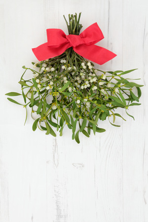 old fashioned: Christmas mistletoe decoration with red ribbon bow over distressed white wood background.