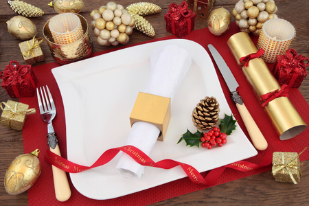 serviette: Luxury christmas dinner table setting with white plate, linen serviette, holly, gold bauble decorations, candles, ribbon and cracker on red place mat over oak background.