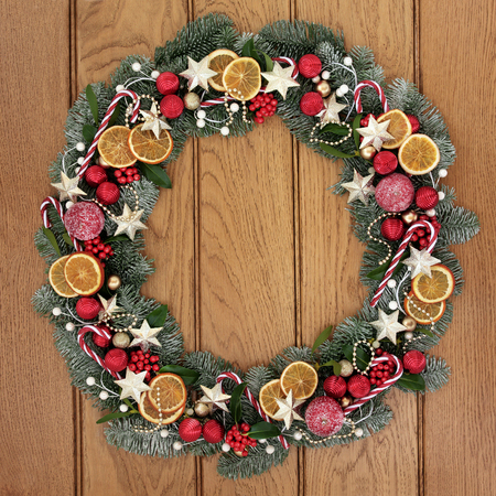 pine  fruit: Christmas wreath with dried fruit, candy canes, gold star and red baubles, holly, mistletoe, pine cones and snow covered blue spruce fir over oak wood front door background.