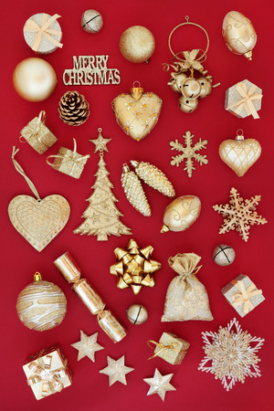 gold christmas decorations: Gold christmas tree decorations and baubles over red background.
