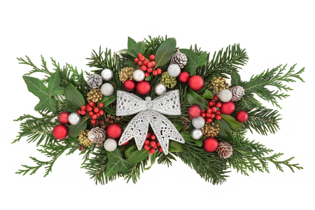 Christmas decoration with silver glitter bow, bauble decoartions, holly and red berries, snow covered pine cones, and winter greenery over white background. Stock Photo